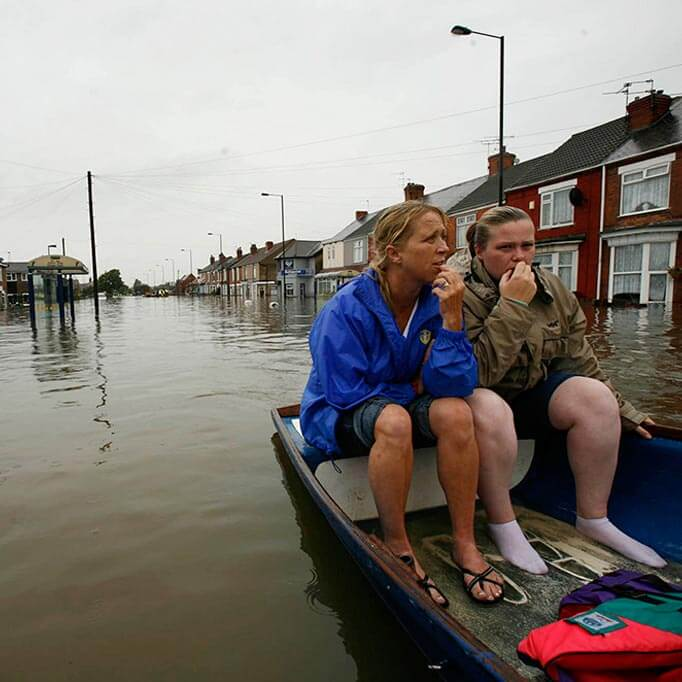 Two women sit in a boat on a flooded street