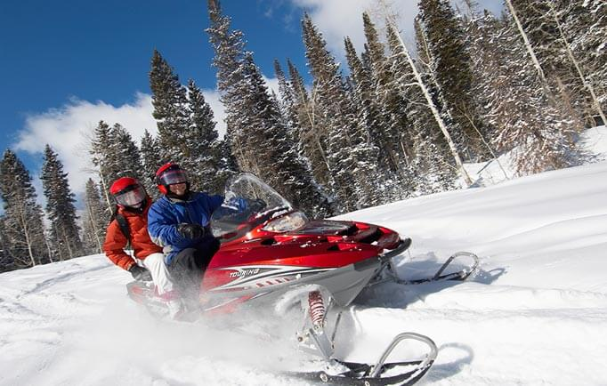 Two people riding a snowmobile through snow
