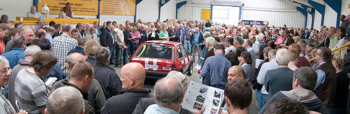 Large crowd at car show surrounding red car at auction