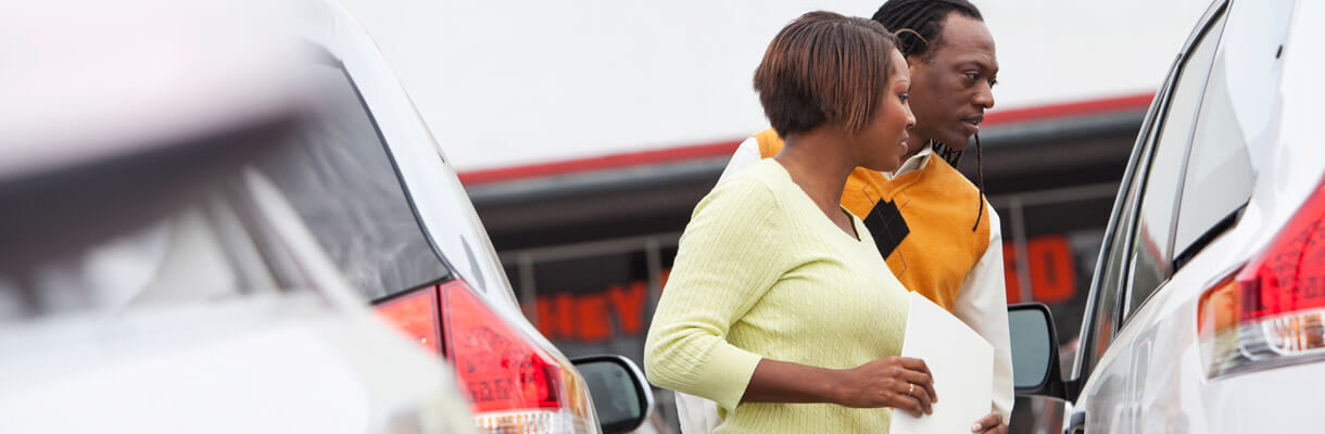 Couple looking through a car window on forecourt