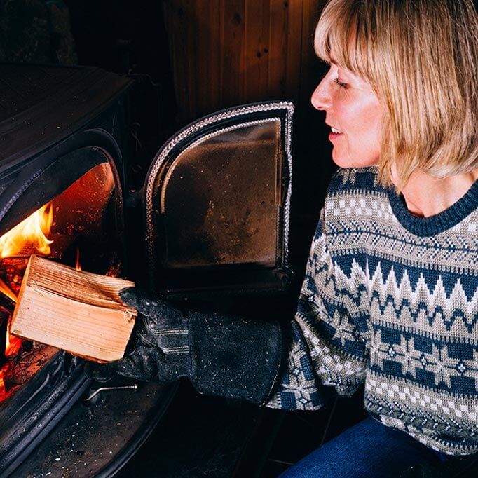 Woman burning wood in log fire