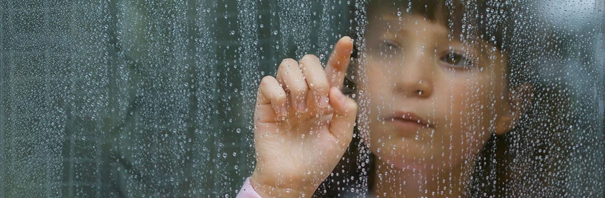 Young girl looking at rainy window and running her finger down it