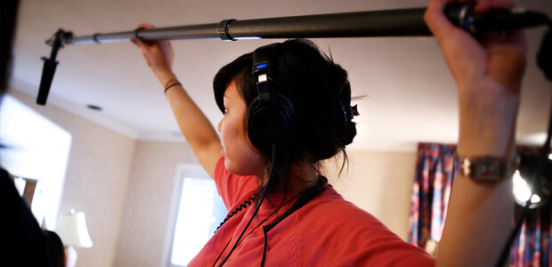 A young woman holding a sound boom