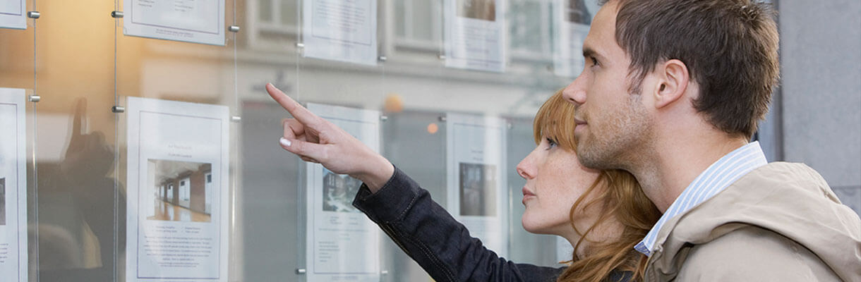 Couple looking for houses through an estate agent window