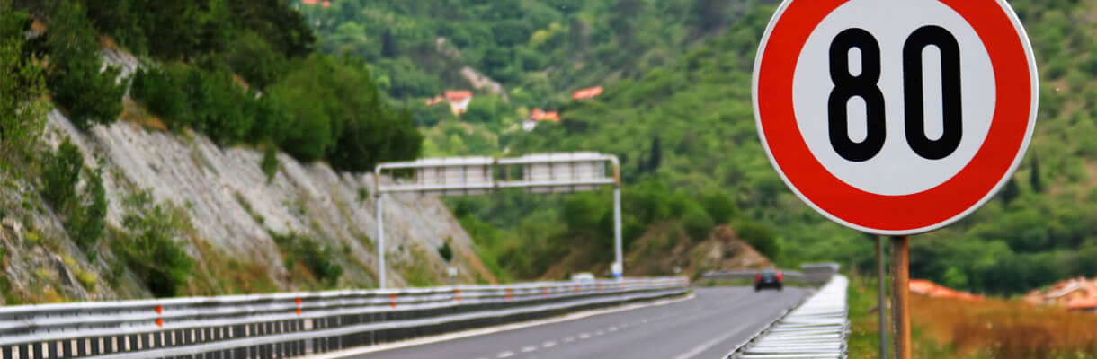 80mph road sign motorway by green trees and mountain