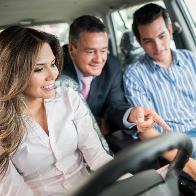 Salesman showing young couple features of a car
