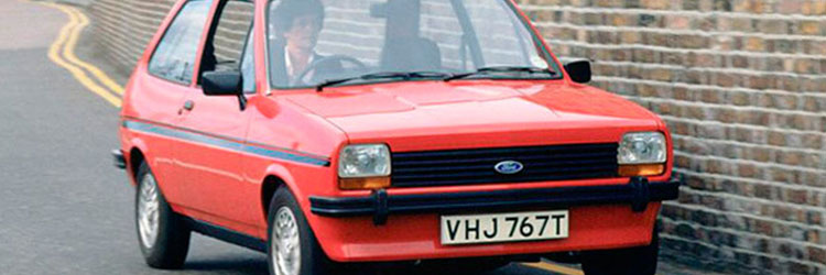 Old Red Ford Fiesta driving by brick wall
