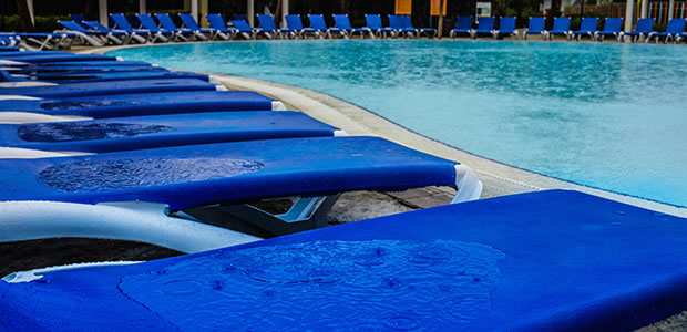 Row of empty sun loungers round a pool, after rain