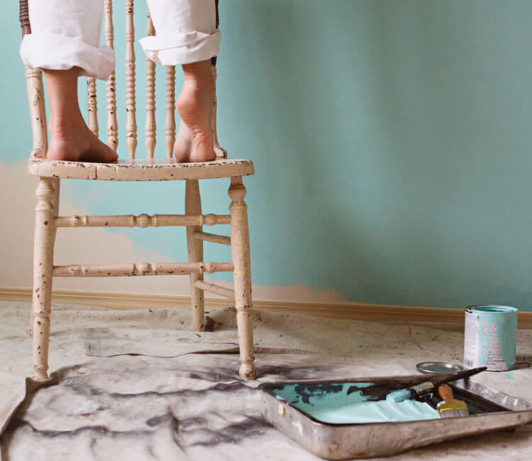 Person standing on wooden stool while they paint