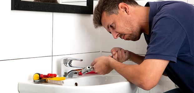 Man fixing leaky tap with a spanner