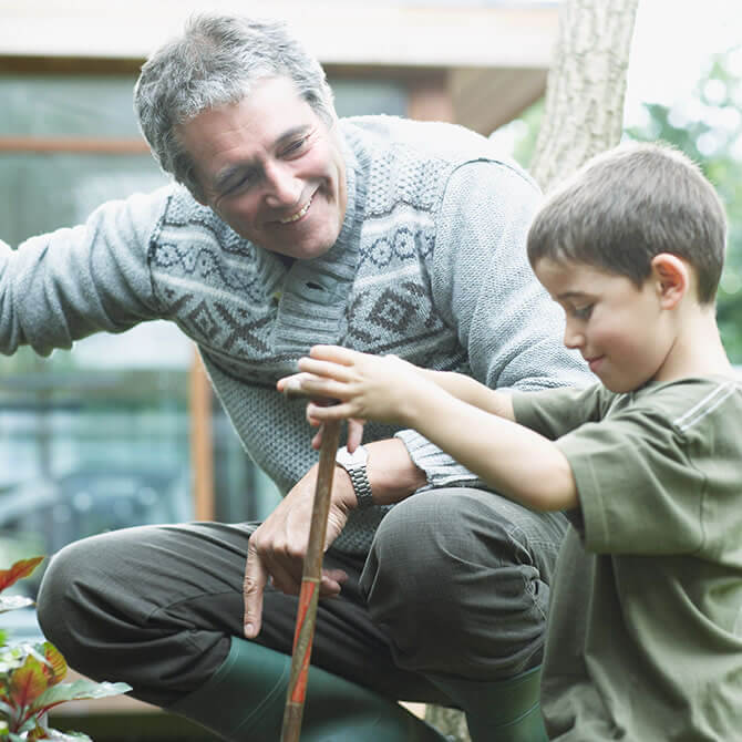 Man and his young grandson gardening