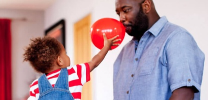 Child holding up a red balloon which the father is inflating in the living room