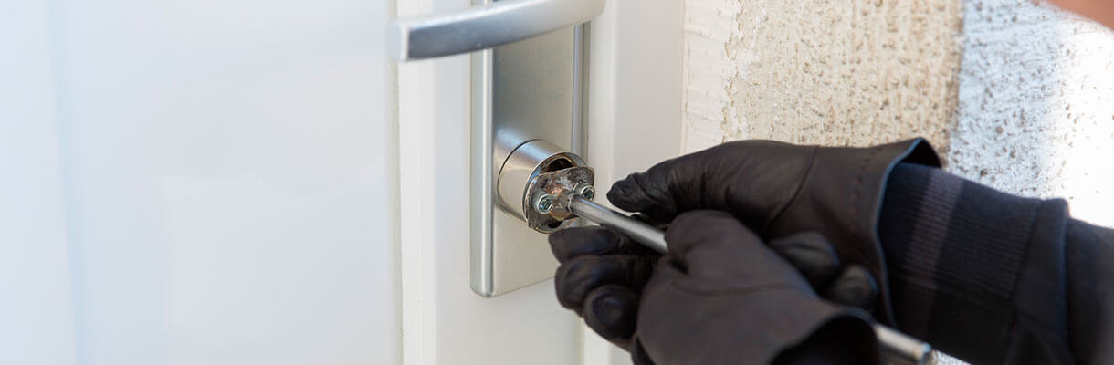 Picking lock of home door wearing black gloves