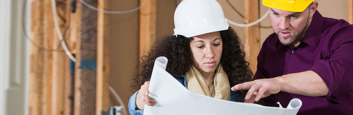 Man and woman looking at construction plans in hard hats