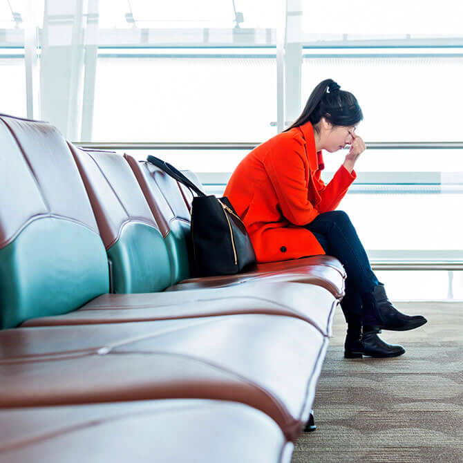 Woman with head in hand sitting on empty row of seats in airport