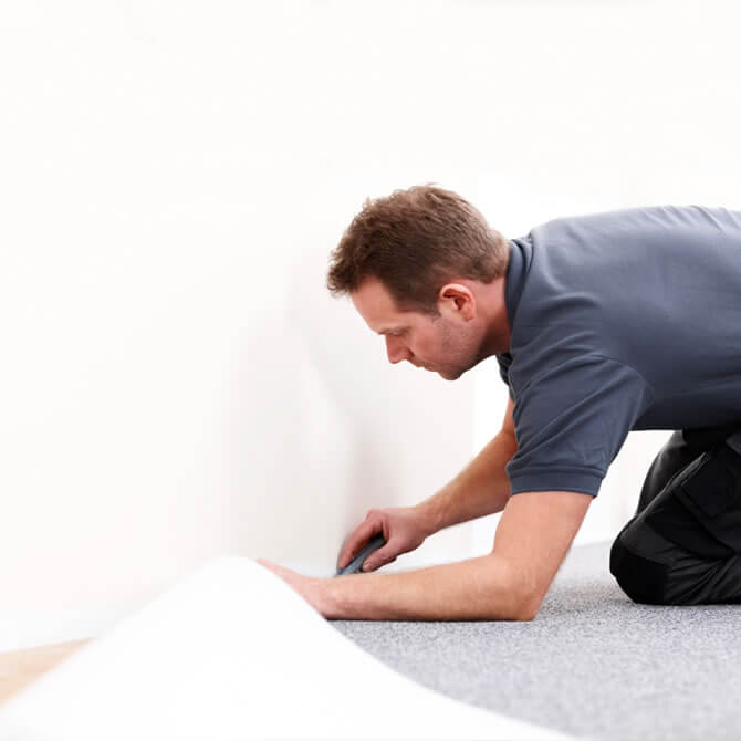 Man fitting grey carpet in a white room