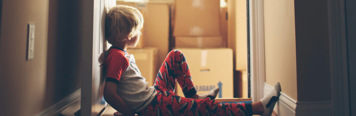 Child sitting next to boxes in his pyjamas