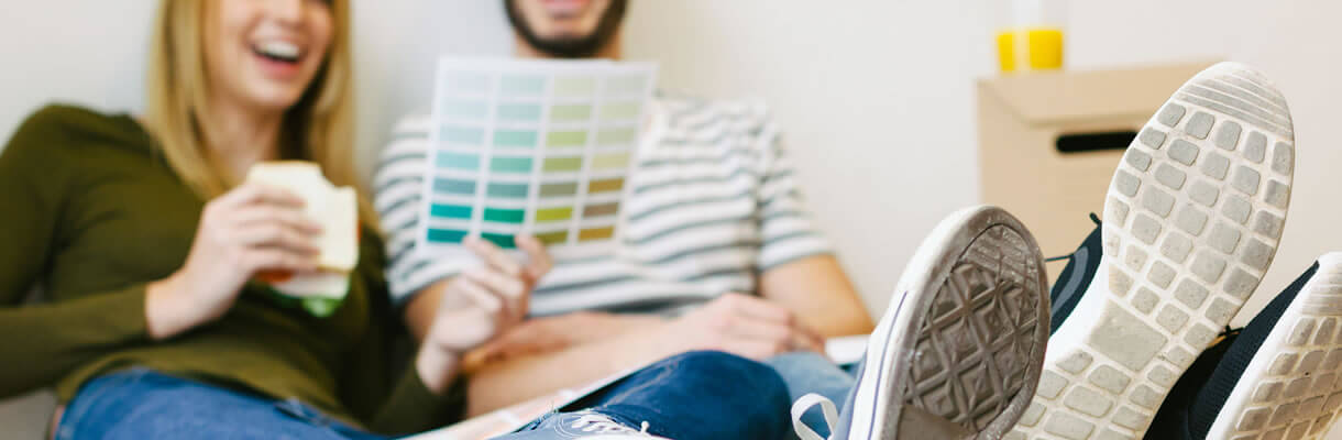 Couple choosing paint colours with their feet up