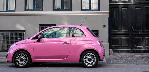 Pink Fiat 500 parked on the road