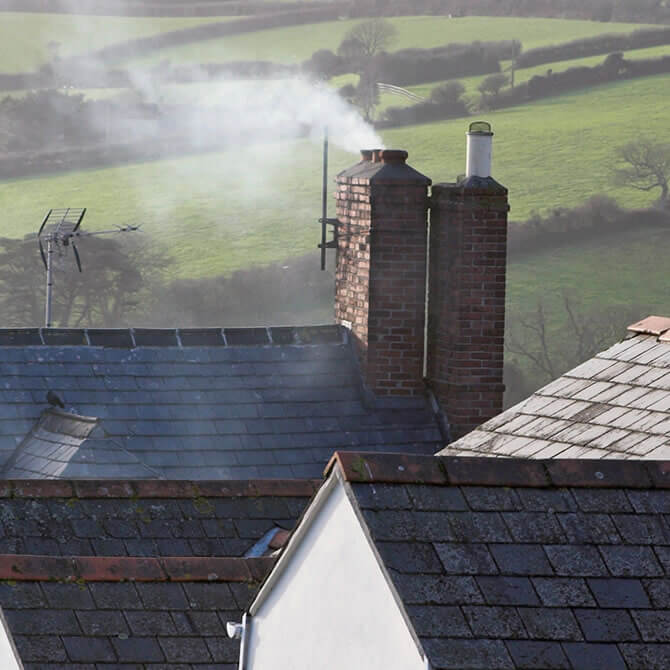 Rooftops, countryside in background, chimney with smoke