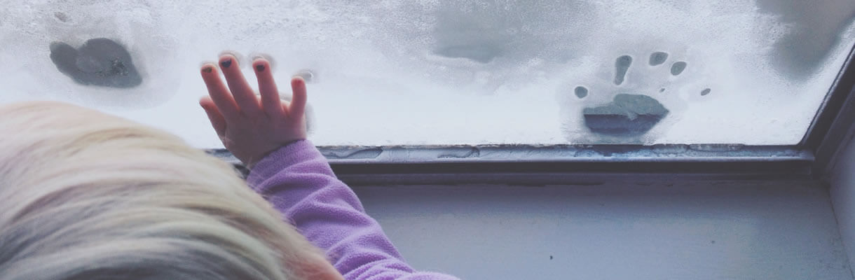 Child in purple handprints on icy window