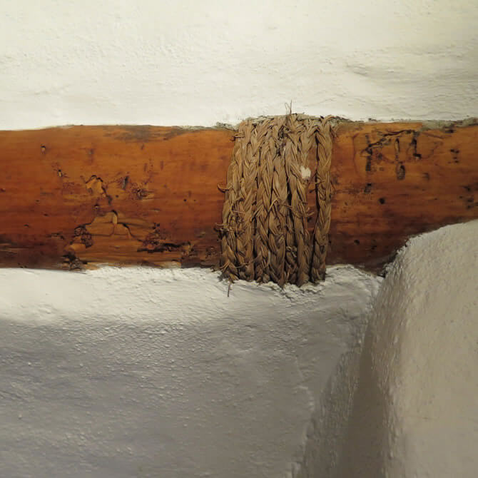Old beam with woodworm on a white building