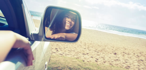 Car on sandy beach with woman seen in side mirror