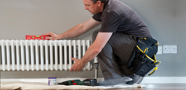 tradesman at work with a white radiator
