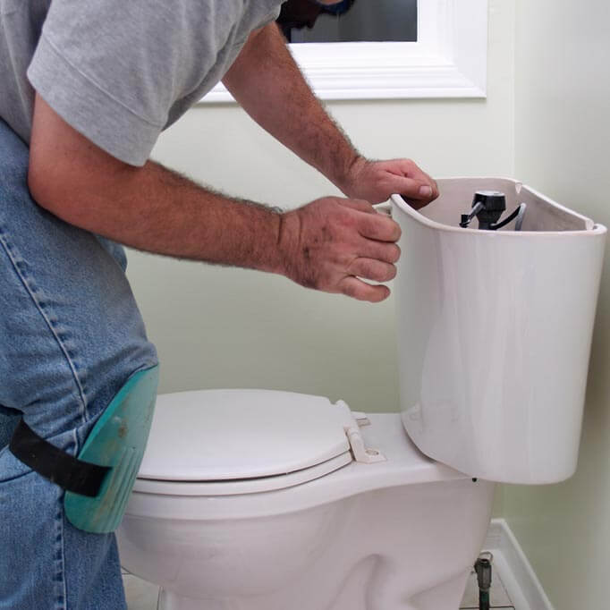 man unblocking a toilet