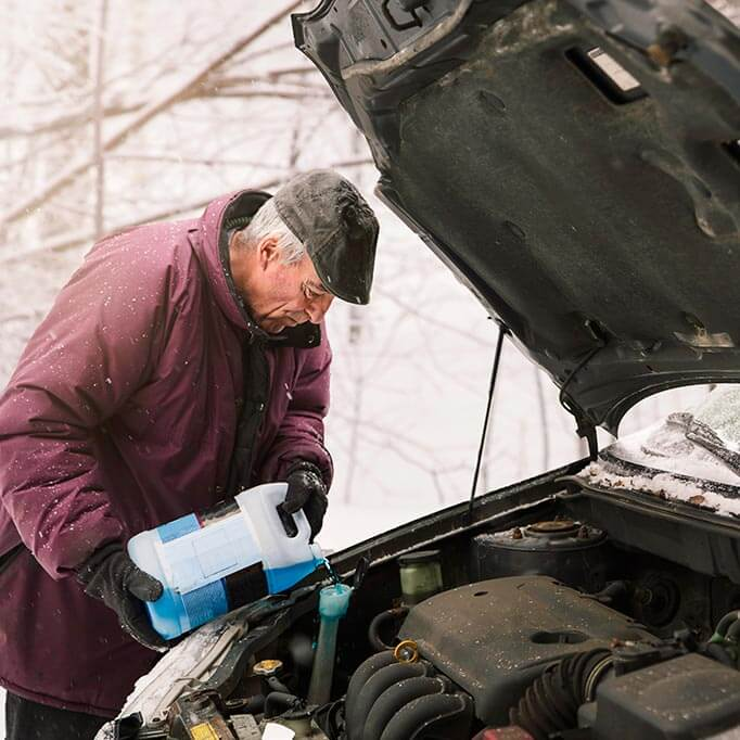 Man topping up anti-freeze in the snow