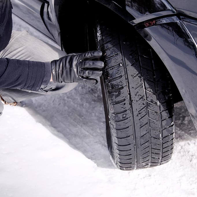 Man checking tyres in snow