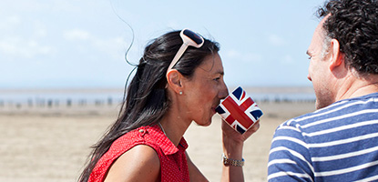 Woman sips from a Union Jack mug on the beach as a man sits beside her