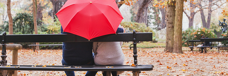 Couple sitting under a red umbrella on a park bench