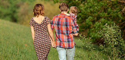 Couple holding hands and child, carried by dad, walk through the countryside