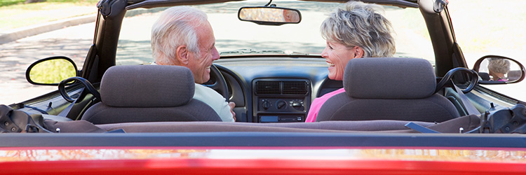 Elderly couple in the car smiling while driving