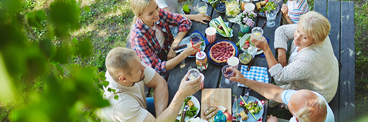 Group of people cheers their drinks as they enjoy a picnic outside on a park table