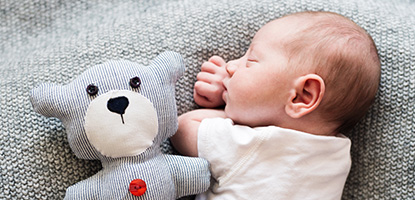 Baby sleeping with black and white striped teddy on a grey bed