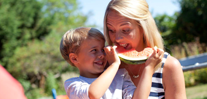 Child playfully feeding his mother some watermelon in the park