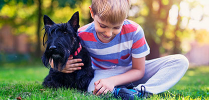 Young boy cuddling his Scottish Terrier in the park